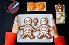 Barns händer som rymmer plattan med lunch i form av monster Arkivbilder