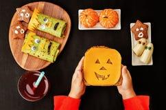 Barns händer som rymmer smörgåsen i form av monster Royaltyfri Bild
