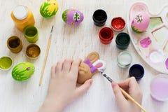 Barns hand målade påskkanin och ägg arkivbilder