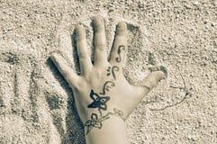 Barns hand med hennatatueringen i sand royaltyfria bilder