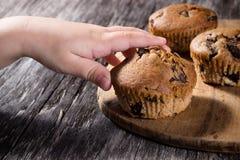 Barns hand som når för en muffin Royaltyfri Bild