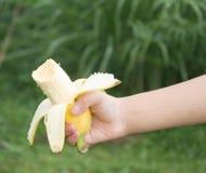 Barns hand som rymmer en banan Arkivbild