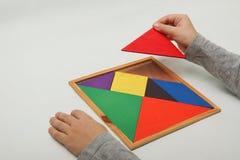 Barns hand som rymmer ett saknat stycke i en tangram arkivbilder