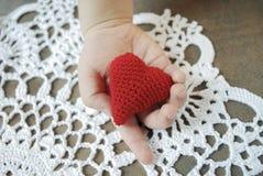 Barns hand som rymmer röd hjärta Royaltyfri Bild