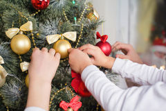 Barns händer dekorerar en julgran Arkivbilder