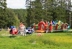 Barns karusell och uppblåsbartrampolin in Royaltyfri Bild