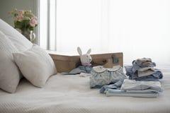 Barns kläder vikt på säng Royaltyfri Fotografi