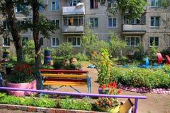 Barns lekplats om ett lägenhethus Arkivfoto