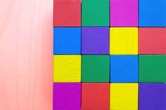 Barns leksak - mångfärgade kuber av buse-huggit ut trä Arkivbild