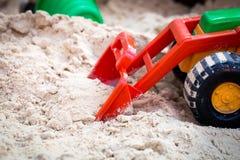 Barns leksakbil i sandlåda royaltyfria bilder