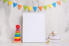 Barns leksaker, med en vit ram ramen på en ljus bakgrund av väggen med barns tecken, för design, orientering Behandla som ett bar royaltyfria foton