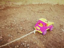 Barns maskin med ett rep i sandlådan royaltyfria bilder