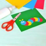 Barns papp tillverkar - den kulöra larven på ett dokument med olika förslagark Sax lim, pappersark fotografering för bildbyråer