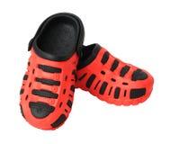 Barns röda rubber sandaler som isoleras på vit Arkivfoton