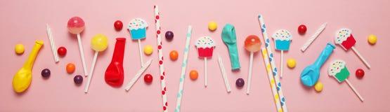 Barns rosa bakgrund f?r f?delsedag Spridda f?rgrika godisar, bollar, stearinljus och sugr?r royaltyfri fotografi