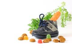 Barns sko med morotvooren Sinterklaas och pepernoten Royaltyfri Bild