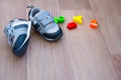 barns skor för nedgång och leksaker på träbakgrund Arkivfoto