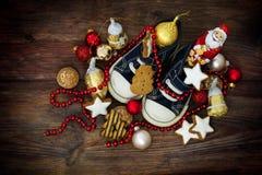 Barns skor fyllde med sötsaker och röd julgarnering Royaltyfri Foto