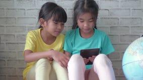 Barns små flickor som hemma använder den smarta telefonen eller minnestavlan arkivfilmer