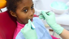 Barns tandläkare undersöker tänderna av lite den gulliga afrikansk amerikanflickan i en röd och gul tand- stol lager videofilmer