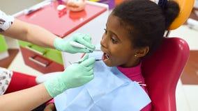 Barns tandläkare undersöker tänderna av lite den gulliga afrikansk amerikanflickan i en röd och gul tand- stol stock video
