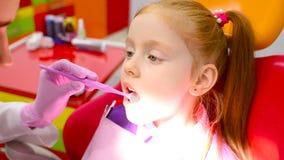 Barns tandläkare undersöker tänderna och munnen av en gullig liten rödhårig flicka i enröd tand- stol arkivfilmer