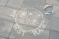 Barns teckning med färgpennor på asfalt - planetjord med mång--färgad blommor och text - min bästa planet royaltyfri foto