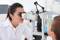 Barns undersökande pys för doktor med ögon- utrustning arkivbild