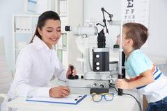 Barns undersökande pys för doktor med ögon- utrustning royaltyfri bild