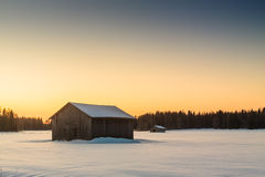 Barns In The Winter Sunrise 1. Two barns in a very cold morning against the late sunrise of the Finnish winter royalty free stock photos