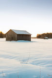 Barns In The Winter Sunrise 3. Two barns in a very cold morning against the late sunrise of the Finnish winter stock photo