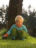 Barnsammanträde i gräs Arkivfoton