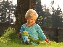 Barnsammanträde i gräs Arkivfoto
