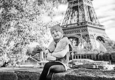 Barnsammanträde på balustraden på invallning nära Eiffeltorn royaltyfri foto