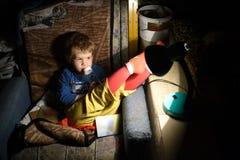 Barnsammanträde på en stol i ett mörkt rum i Front Of The Lamp royaltyfri bild
