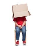 Barnsammanträde på en stol med stort boxas det dolda huvudet Arkivbilder
