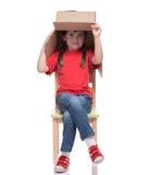Barnsammanträde på en stol med stort boxas det dolda huvudet Arkivfoton