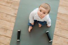 Barnsammanträde på yoga som är matt med hantlar som ser kameran Arkivbilder