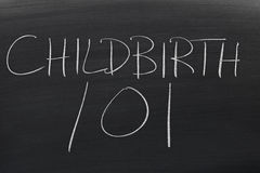 Barnsbörd 101 på en svart tavla Royaltyfri Fotografi