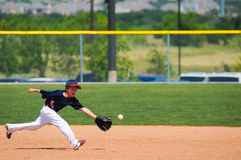 Barnserien i basebollpojken ner ut för att fånga för att klumpa ihop sig Arkivbilder