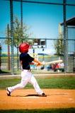 Svängande slagträ för barnserien i basebollspelare Arkivbilder