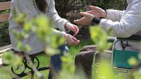 Barnserviceflicka som rymmer handen av den äldre kvinnan i en rullstol stock video