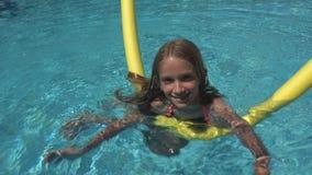 Barnsimning i pölen som ler ungen, flickastående som tycker om sommarsemester arkivfoton