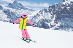 Barnskidåkning i bergen Ungen skidar in skolan Vintersport för ungar Familjjulsemester i fjällängarna barn lärer royaltyfri foto