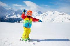 Barnskidåkning i bergen Ungen skidar in skolan Vintersport för ungar Familjjulsemester i fjällängarna barn lärer royaltyfria foton