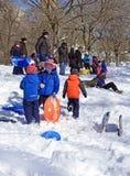 Barnsläderidning i snön Arkivbild