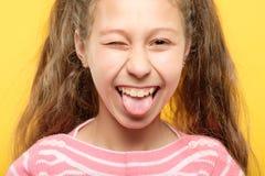 Barnsligt uppförande för lycklig glad flickapinnetunga arkivbilder