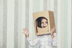 Barnsmå flickor som spelar astronautet i en papphjälmportr royaltyfria bilder