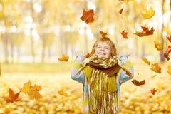 Barnstående i Autumn Park som ler lyckligt spela för liten unge arkivbild