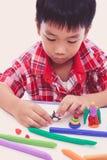 Barnstöpningsval som modellerar lera, på vit bakgrund Arkivfoton